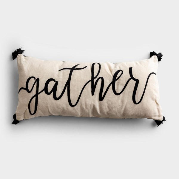 """This neutral black and white throw pillow is perfect for gathering family and friends on your cozy couch. This embroidered pillow with the word """"Gather"""" is complemented by the black fringe tassels adorning the corners of the lumbar pillow."""