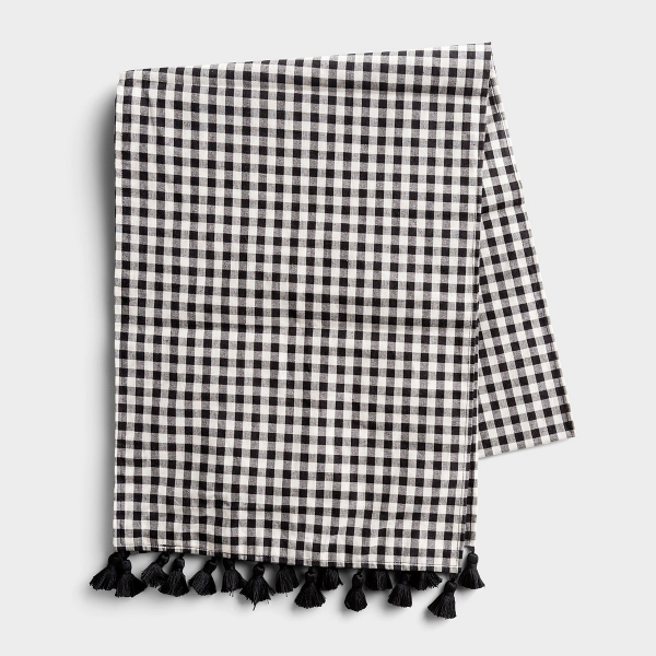 Dress up your table with this black and white check table-runner. Perfect for all occasions and holidays, the fun black fringe tassels give this table-runner a playful design element.